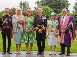 Rain means changes to Queen's reception