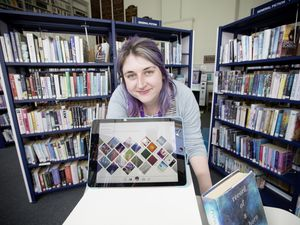 Guille-Alles Library assistant Beth Brown with a screen which shows the most popular titles read via the Libby app, which came into use on 23 March. (Picture by Adrian Miller, 29474272)