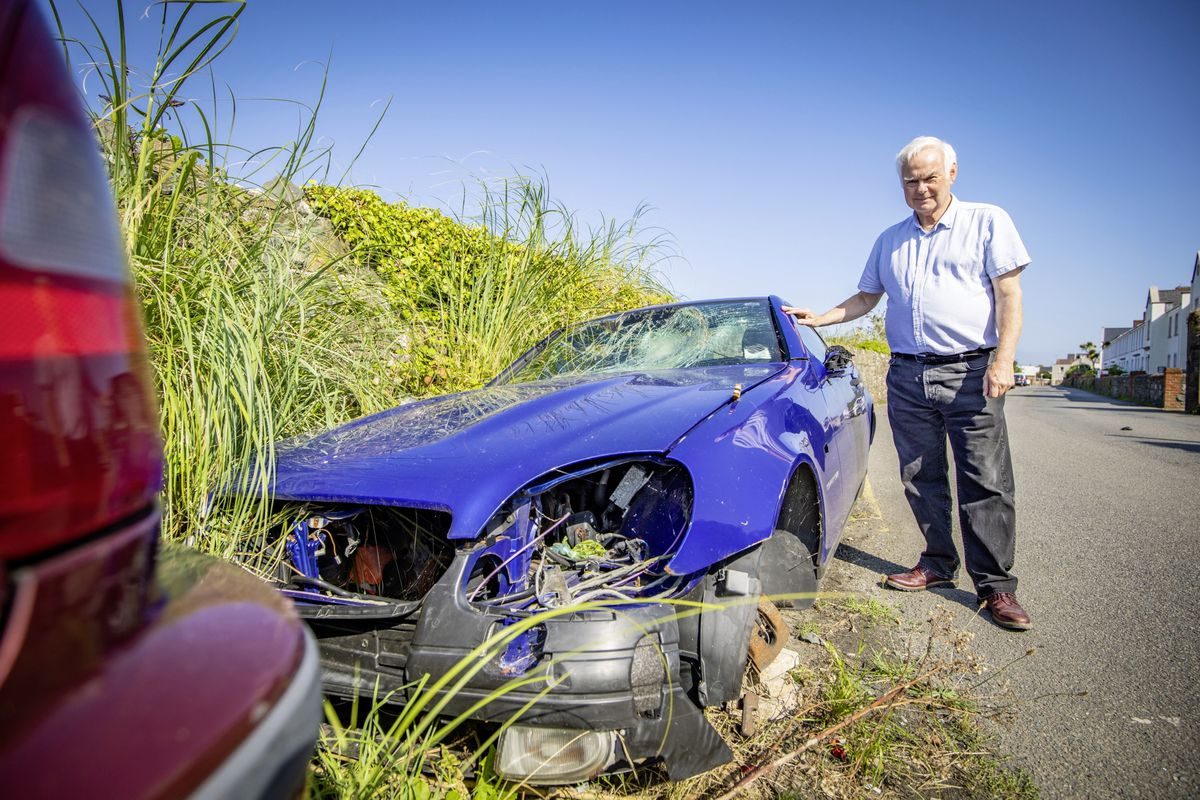 St Sampson's parish constable Paul Le Pelley with one of the seven abandoned cars along Saltpans that have lain there for years. The parish wants the vehicles removed by their owners before 15 September. (Picture by Sophie Rabey, 29915746)
