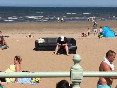People are loving this extreme sunbather sat on a sofa on the beach in Scotland