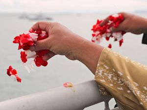 Relatives of plane crash victims cast flowers into Indonesia sea
