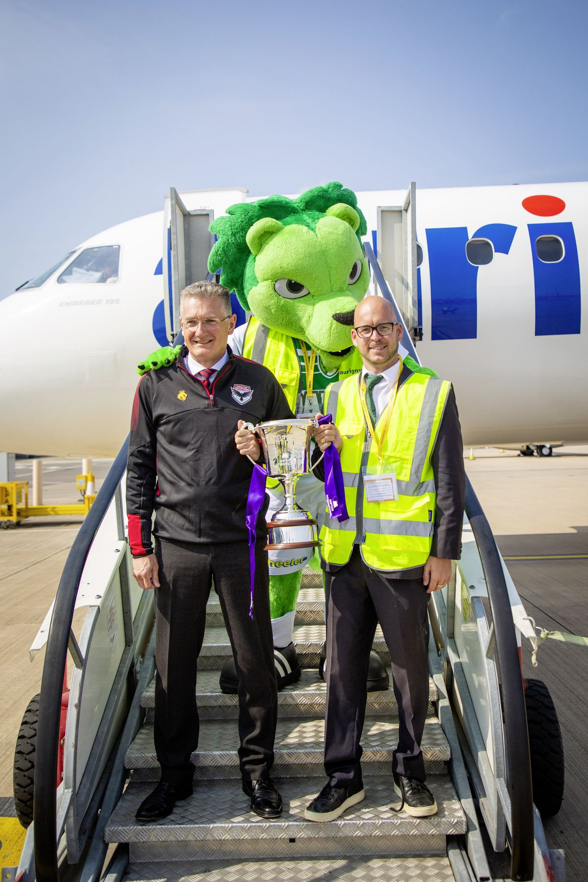 FC Isle of Man chairman Gary Weightman, left, with Guernsey FC director Nic Legg and Roary the Lion on the Aurigny jet's steps. (28678581)