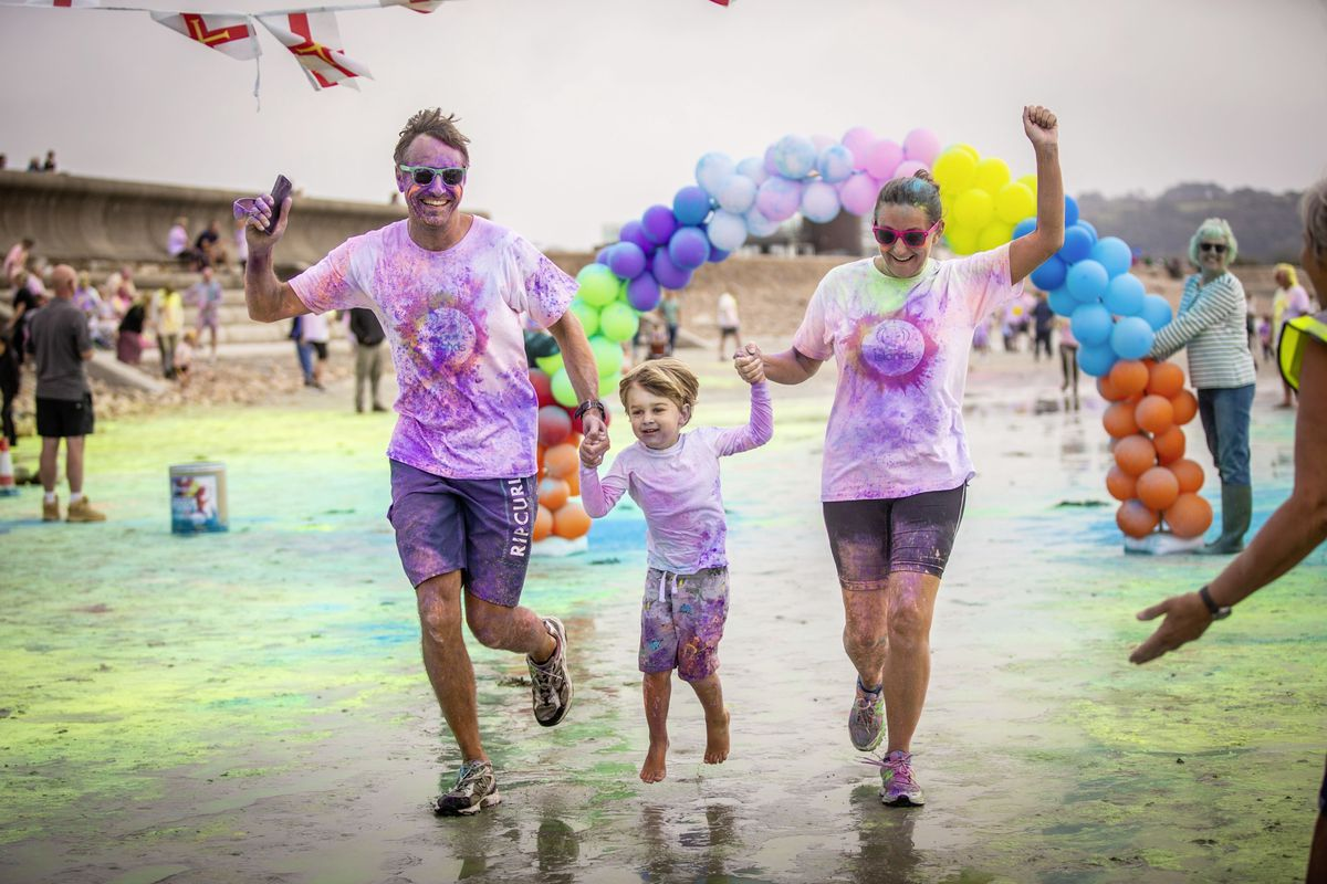 Picture by Sophie Rabey.  19-09-20. Islands Insurance have sponsored a Colour Run on Vazon Beach to help raise money for Guide Dogs for the Blind. Blair Woodward, Barney Woodward (3 and a half) and Tamzin Woodward through the finish line.. (28707312)