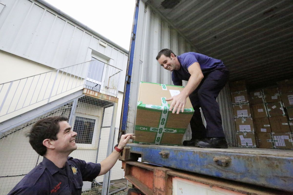 Fire crew Craig Mollet, left, and Jason James loading the shoeboxes on Saturday. (Picture by Adrian Miller, 28886947)