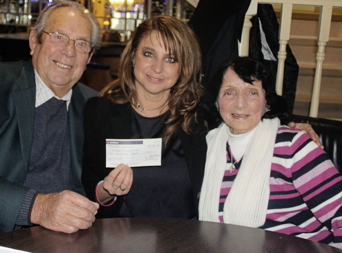 Jo Priaulx holding the prize-money cheque donated to the Priaulx Premature Baby Foundation by Bert and Brenda Fallaize