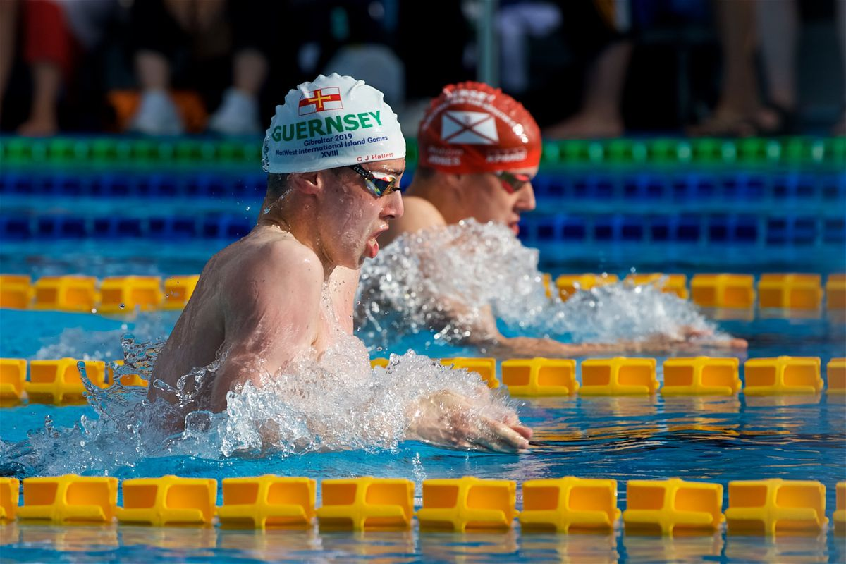 Breast to breast in Gibraltar: Big Channel Island rivals Charlie-James Hallett and Robert Jones push hard in the men's 200m breaststroke. Neither man will see much competitive action this calendar year. (Picture by Rob Currie, 28437975)