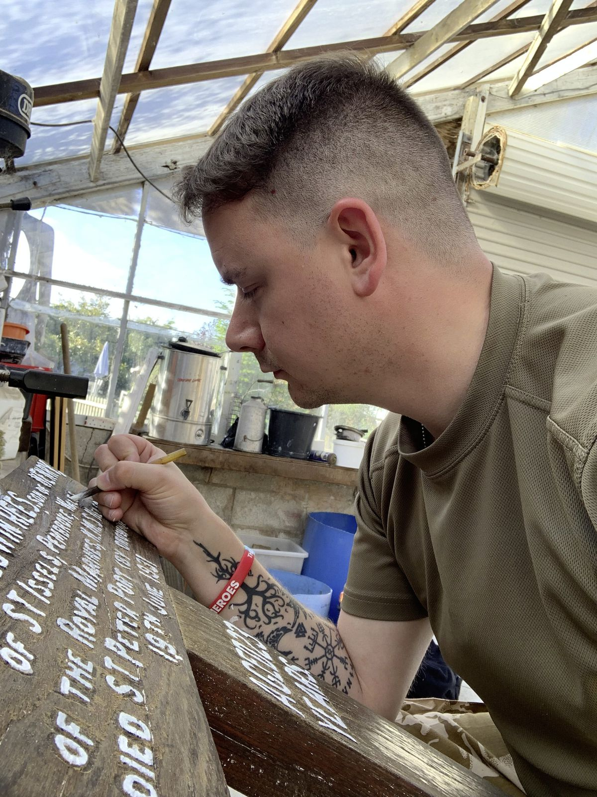 Matt Hill, a sergeant with the Guernsey Royal Marines Cadets, who says he has the marine corps in his blood, repainting the inscription on the cross.