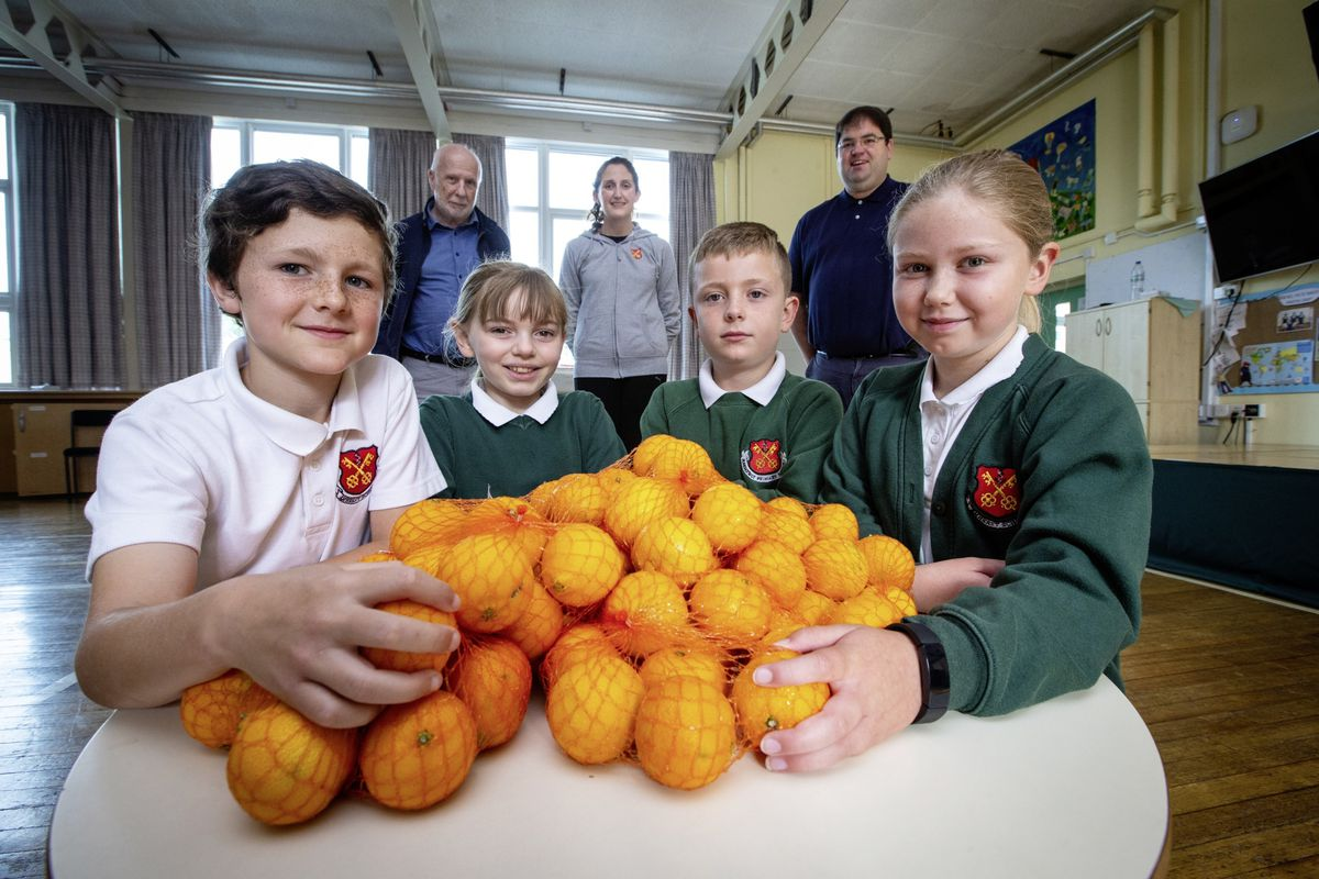 Les Cotils is supplying Fruit for Schools on a regular basis to provide students with a healthy snack. Left to right, Jaylen Leadbeater, Erica Bourgaize, both 9, Alfie Bourgaize, 8 and Alba Cheetham, 9. Behind them are, left to right, Tony Gallienne, Les Cotils chairman, Year 4 teacher and PSHE lead Lucie Le Prevost, and Steven Le Prevost from PWC. (Picture by Peter Frankland, 29727816)