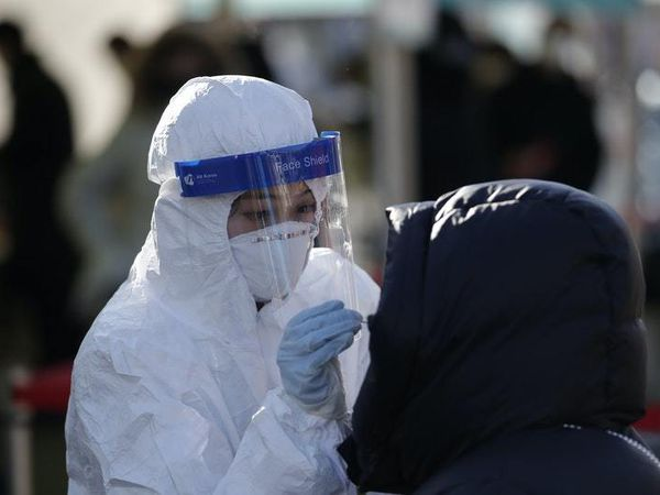 A medical worker wearing protective gear takes a sample from a woman during a Covid-19 testing. (29110468)