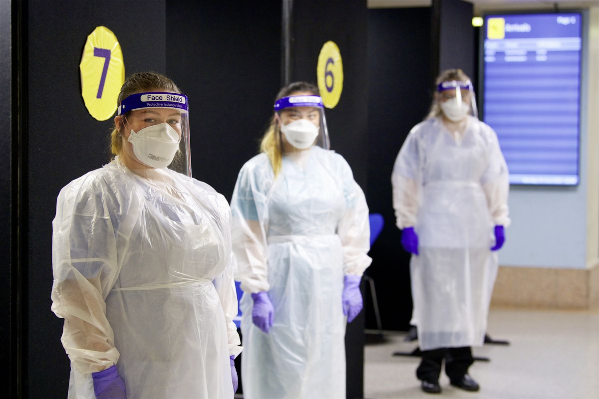 Arrivals to Jersey will now be tested on day zero, five and ten for Covid-19. Left to right: Elouise Hargeaves, Chloe Durrant and Leisha Maguire in full PPE. (Picture by Rob Currie, 28919039)