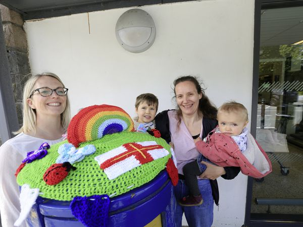 Tamara O'Brien, holding children Ethan, 3, and Caoimhe, 1, a self-proclaimed beginner, made the crochet topper for the Rohais post box. She is pictured with Dawn Gallienne, head of corporate engagement at Guernsey Post.                                                                     (Pictures by Adrian Miller, 29524890)