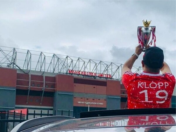 Liverpool fan takes replica Premier League trophy for photo at Old Trafford