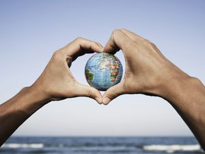 closeup of a young caucasian man with a world globe in his hands forming a heart against the blue sky, in front of the sea (29277630)