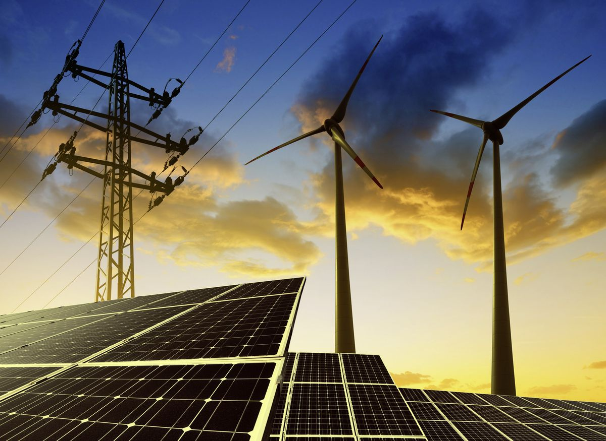 Solar panels with wind turbines and electricity pylon. (Picture by jaroslava V/Shutterstock)