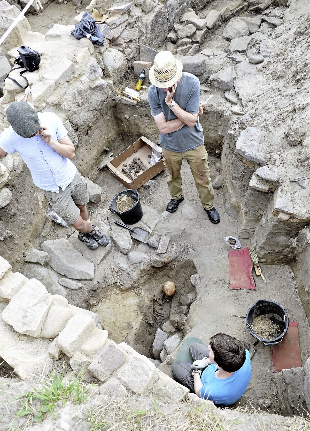 States archaeologist Phil de Jersey, in the straw hat, examines one of the Alderney skeletons. Photo: David Nash. (29471665)