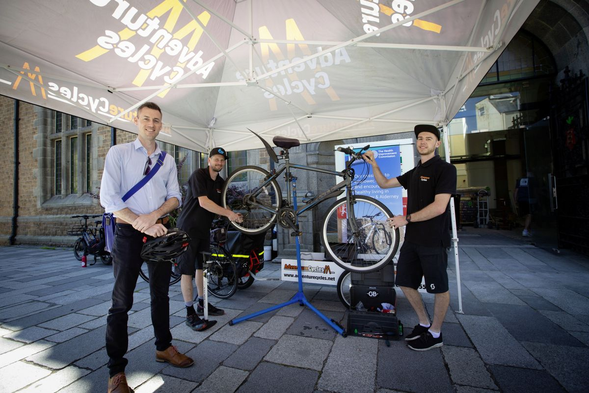 Mark O'Neill, left, has his bicycle checked over by Adventure Cycles' Dan Thwaite and Joe Collenette, right. (Picture by Cassidy Jones, 29772648)