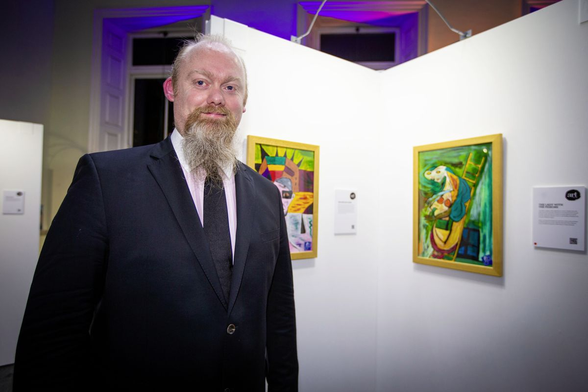 Art for Guernsey founder David Ummels with some of the prisoners' work in the free exhibition, entitled Double Window, which is at the Guille-Alles Library. (Pictures by Sophie Rabey, 26922075)