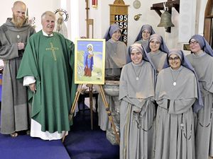 Parish Canon Michael Hore blessed a painting of 'Our Lady of Alderney,' an iconic painting by Annette Ashton Melzack, as his final act before retirement. The painting features a blonde hedgehog and barbed wire, and was gifted to St Anne's Catholic Church. Image by David Nash.  (29658527)
