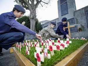 Planting poppy crosses at the War Memorial to commemorate Old Elizabethans who died in two world wars are present-day CCF members, left to right,  Oliver Coupe, 16, James Kennedy, 15, and Max McCarthy, also 15. (Picture by Sophie Rabey, 28885377)