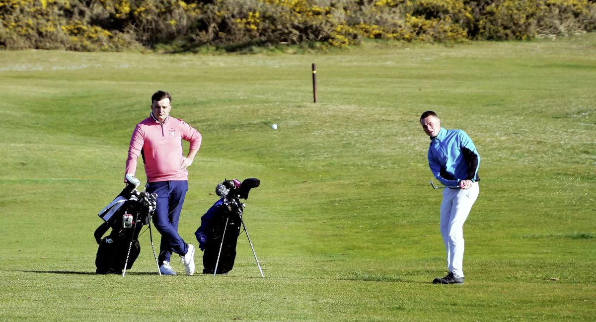 Jake Marshall chips watched by playing partner Jeremy Nicolle in their win over Roland Mills and Rory McKenna yesterday at L'Ancresse. (Picture by Gareth Le Prevost, 29510724)