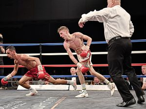 Bradley Watson floors Loua Nassa with a big right-hander in their English super-flyweight title contest in Sheffield on Friday. Watson's coach, Paul Rees, can be seen in the white shirt in the red corner. (Picture by Keith Turner)