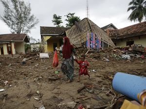 A woman and her child walk past debris at a tsunami-ravaged area in Carita, Indonesia. Money from the Guernsey Overseas Aid Commission has been paid to the Disasters Emergency Committee to help in its relief work. (Picture by AP Photo/Achmad Ibrahim)