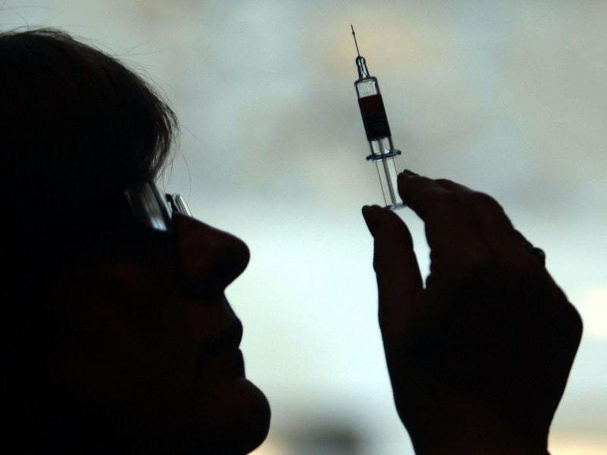 A nurse preparing to give a patient a vaccine (28850332)