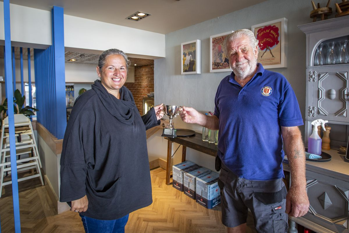 St Peter Port constable Zoe Lihou presenting Geoff Le Gallez with the GY1 Constables Cup for his Liberation Day decoration celebrations outside of his house. (Picture by Sophie Rabey, 29734902)