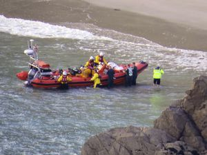 The injured person is placed on the bow of the RNLI inshore lifeboat, Elizabeth and Margaret Milligan, after receiving treatment on the beach from paramedics. (Picture by Tony Rive)