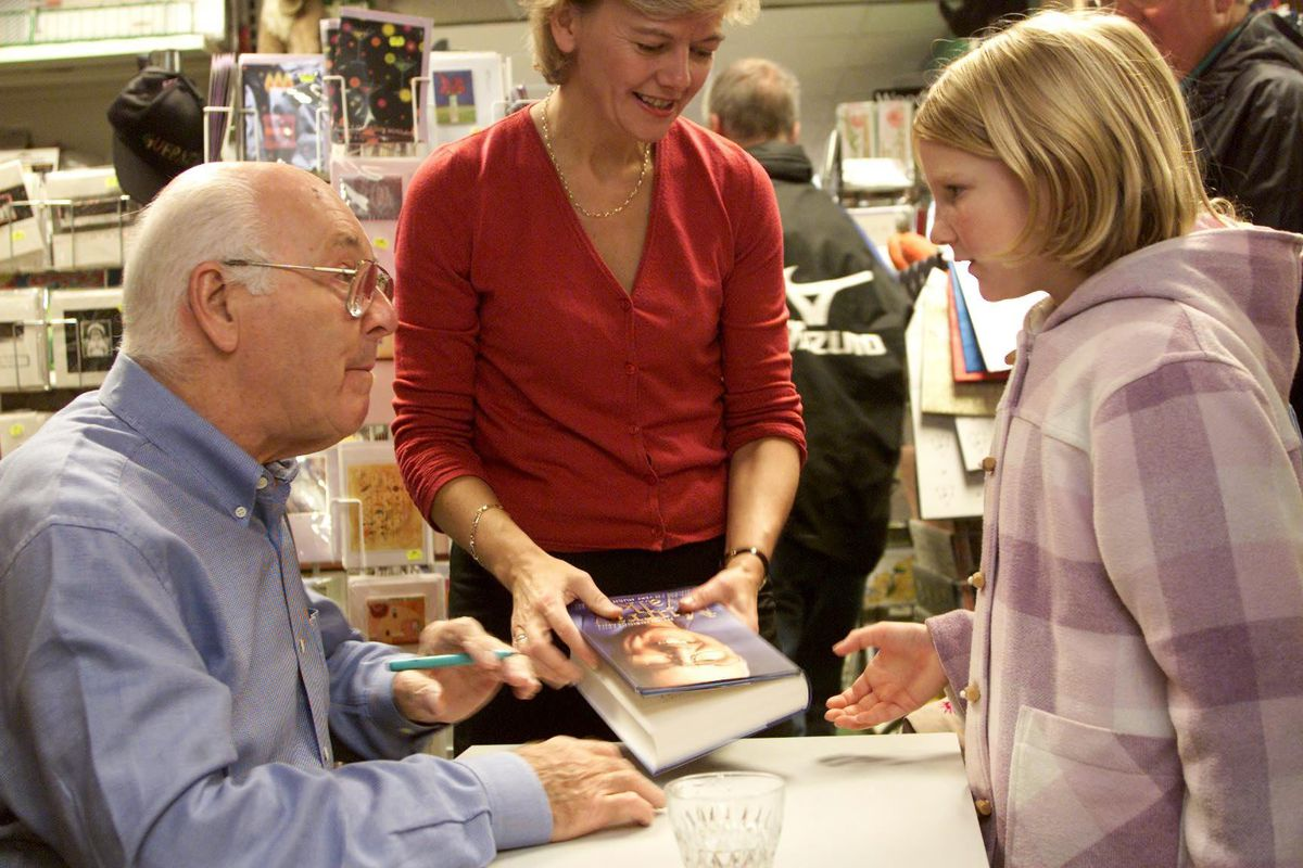 Murray Walker signing a copy of his autobiography, Unless I'm Very Much Mistaken, for Jessica Rabey aged 9 in 2002. Standing between them is his PA, Jane Beaton. (Pictures by Adiran Miller, 29332897)