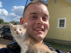 Police officer uses hat to save kitten trapped in car wheel