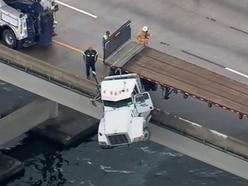 In video: Truck cab dangles over side of bridge after crash