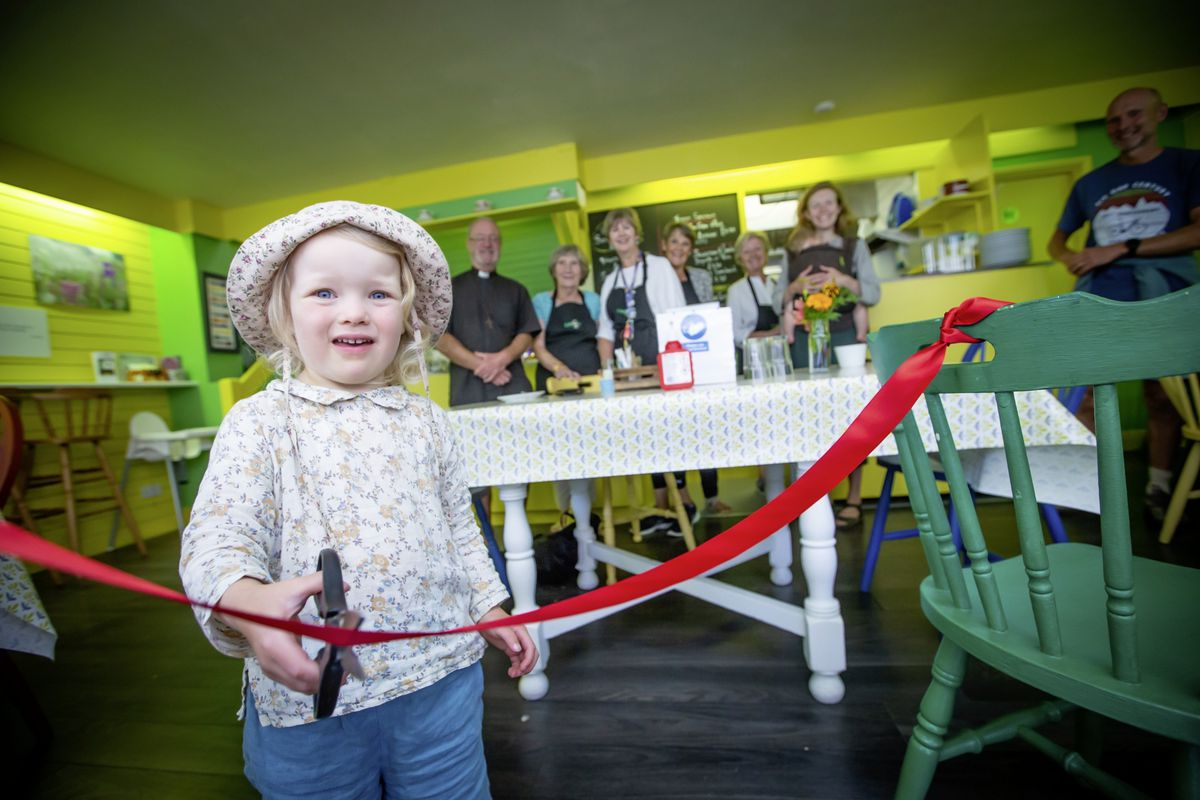 Leonore Bouchet-Hibbert cuts the ribbon at the re-opening of Caritas Cafe yesterday. The community cafe had been closed since March. (Picture by Peter Frankland, 28647163)