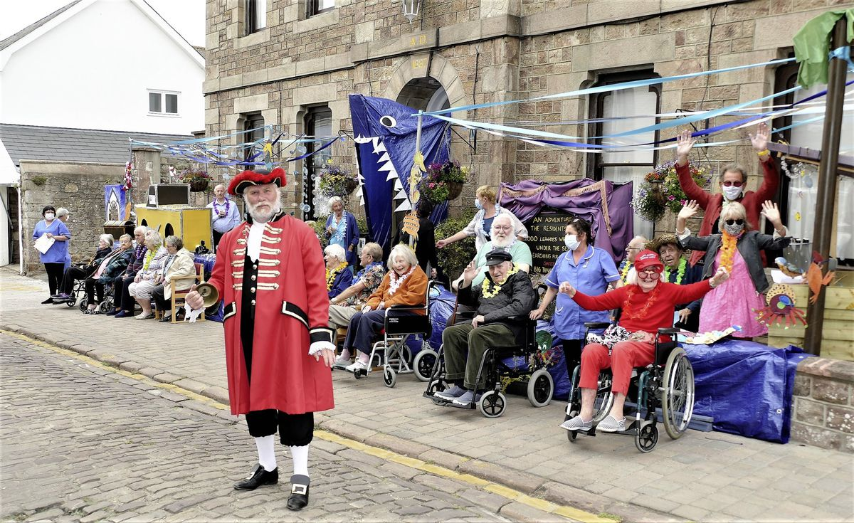 Alderney town crier Kevin Moore prepares to give the traditional Loyal Address in front of the Connaught Care Home's static float, which was the only one in the 'Not The Alderney Week' cavalcade. Alderney President William Tate and his wife Gabrielle are pictured on the extreme right, suitably masked. (Picture by David Nash)