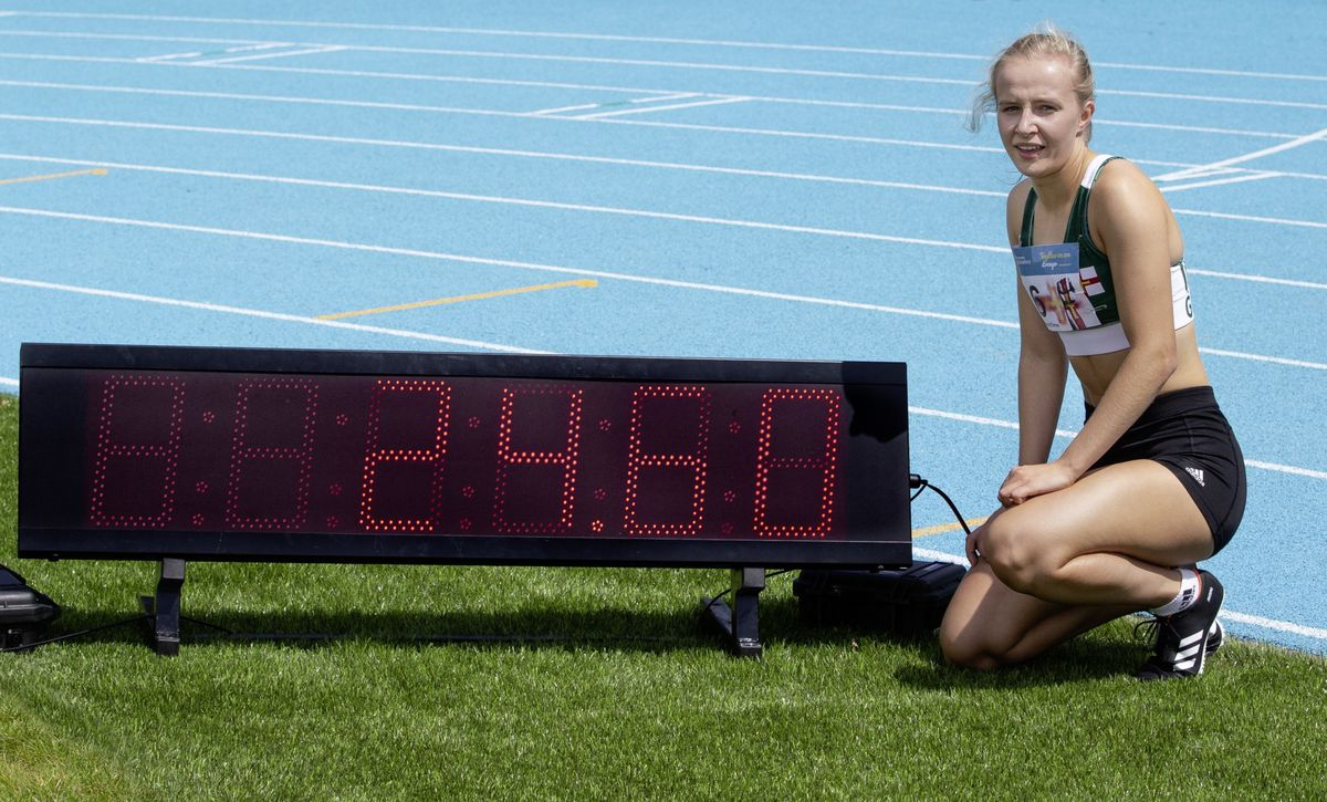 Abi Galpin next to the clock which is displaying her new women's 200m Island record time. (Picture by Martin Gray, www.guernseysportphotography.com, 28536314)