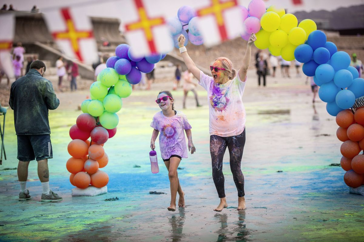 Picture by Sophie Rabey.  19-09-20. Islands Insurance have sponsored a Colour Run on Vazon Beach to help raise money for Guide Dogs for the Blind. Eden Knowles Ahmed (8) and Caroline Knowles Ahmed through the finish line. (28707310)