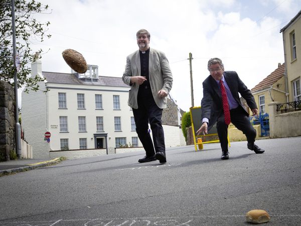 The Dean, the Very Rev. Tim Barker, left, and Bailiff Richard McMahontry their hand at throwing or rolling bread during the Lammas Day celebrations. (Pictures by Cassidy Jones, 29824601)