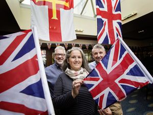 St Peter Port constable Zoe Lihou with bunting and flags to encourage people to decorate their properties for Liberation Day. She is pictured at Rocquettes Hotel with operations manager Calum Le Noury and Derek McNulty hotel manager. (Picture by Adrian Miller, 29515803)