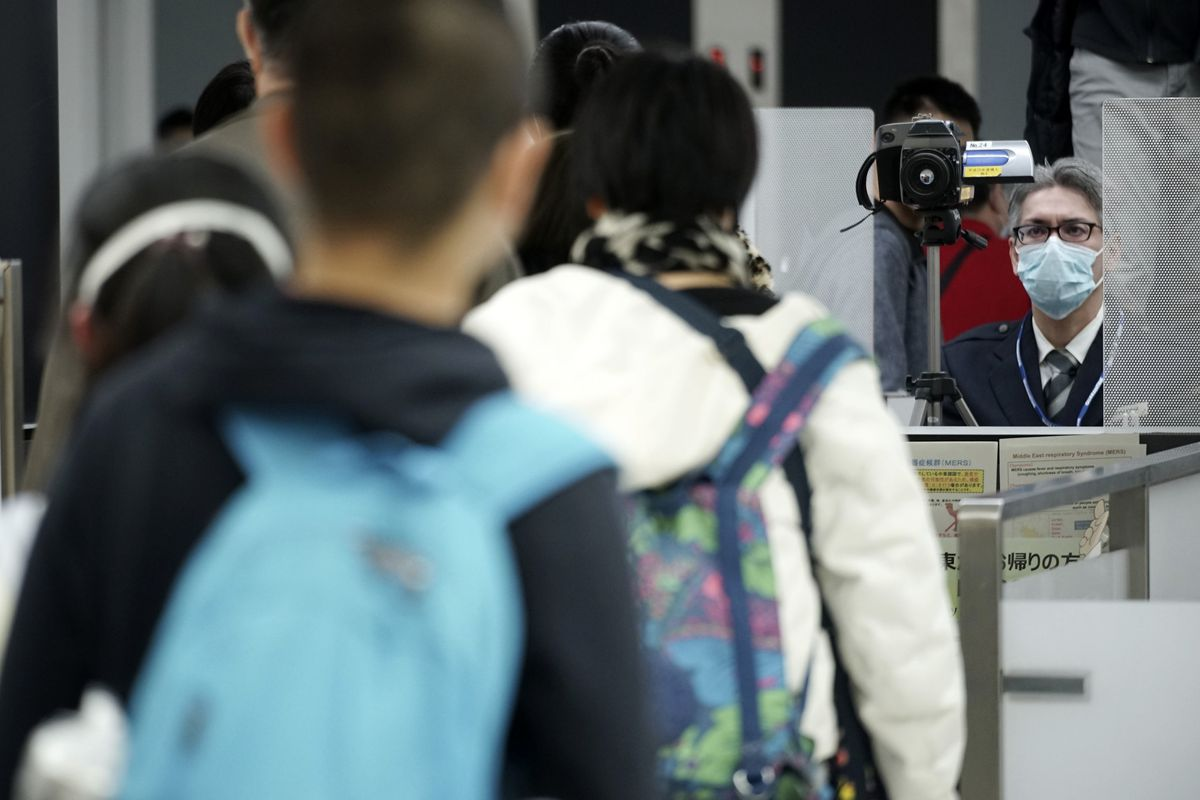 Quarantine staff, right, monitor travellers from China's Wuhan and other cities as they go through body temperature scanners at Narita international Airport, near Tokyo. China has closed off the city of more than 11m. people in an unprecedented effort to try to contain the deadly coronavirus. (AP Photo/Eugene Hoshiko)