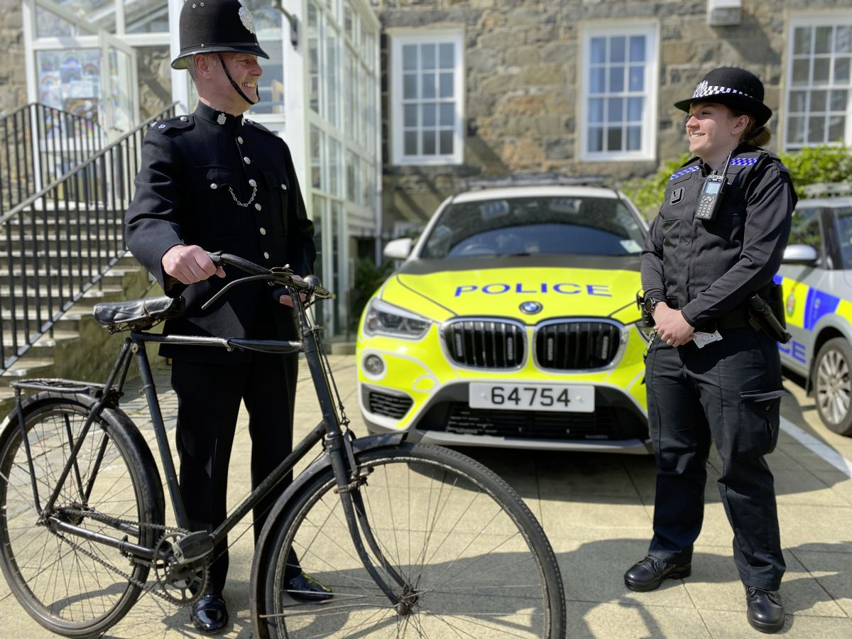 Legal compliance officer Trevor Coleman in 1920s uniform and bike, alongside student officer Aimee Le Bachelet in current uniform in front of a response vehicle.