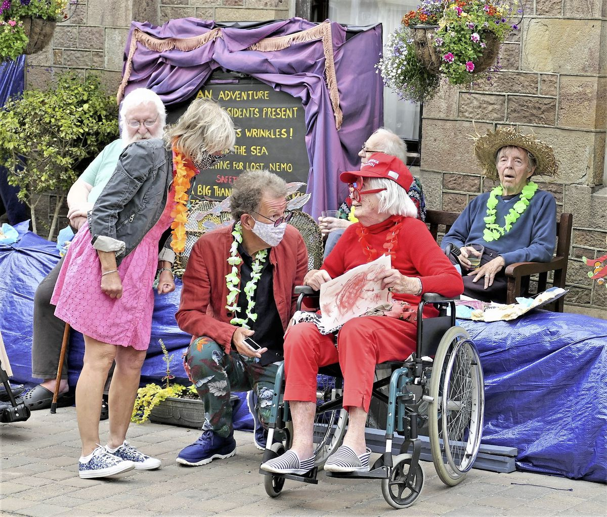 Alderney's President William Tate and his wife Gabrielle, discuss the finer points of the Connaught Home's static float with 100-year-old Pauline Gladwell, suitably outfitted for the occasion. (Photo by David Nash)