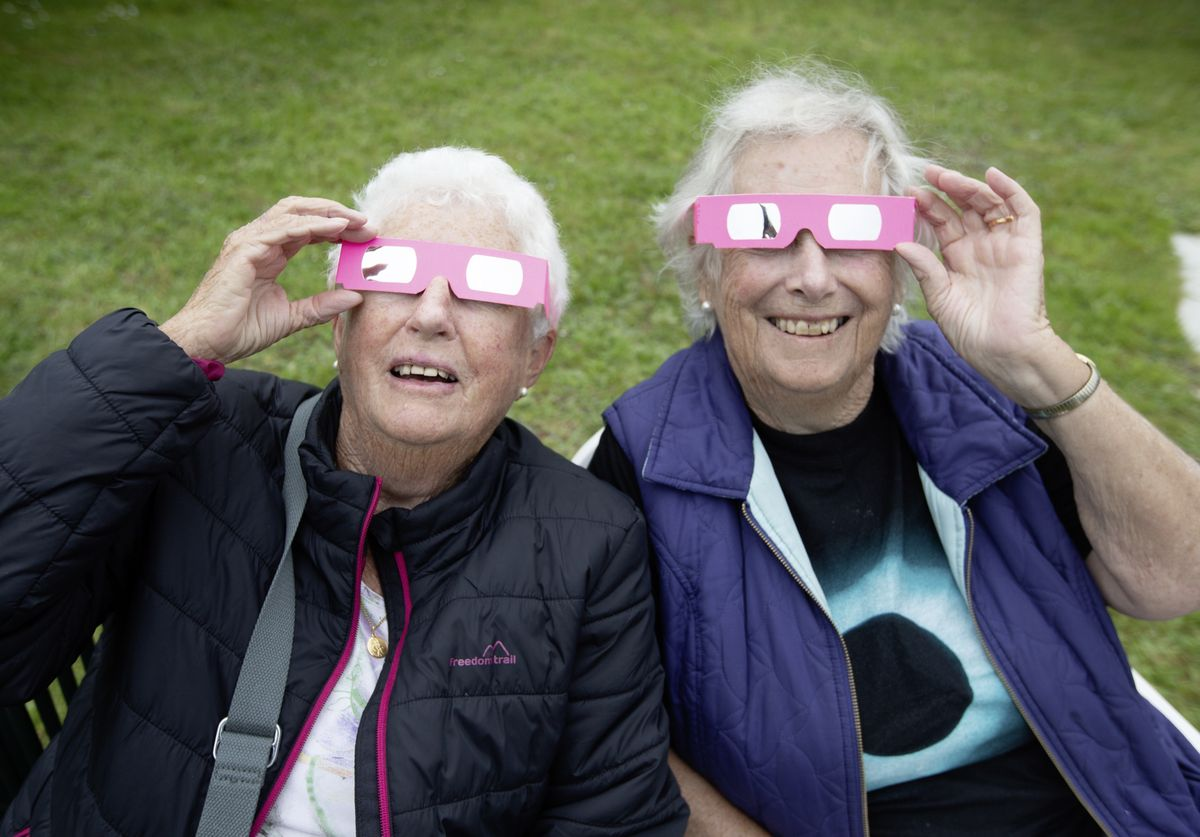 Patsy Self, left, and Mary Thompson were two of those using special eclipse viewing glasses as conditions did not allow La Societe's telescopes to be used. (29640983)