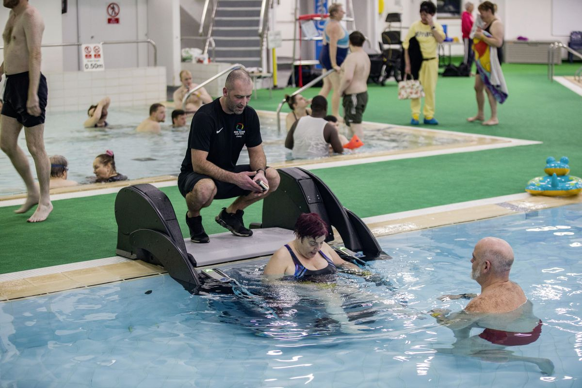 Danny Le Page, poolside, and Adrian Sarchet, in the water, watch as Guernsey Disability Swimming member Sandra Robilliard uses the PoolPod to get into the pool. (29113801)