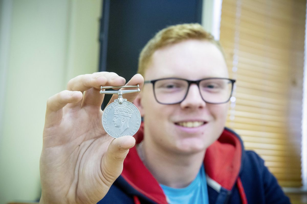 Ben Spinks, Cashier at Batif with a WWII medal which they found within a pile of coins donated to the Channel Islands Air Search charity campaign. (Picture by Peter Frankland, 28908522)