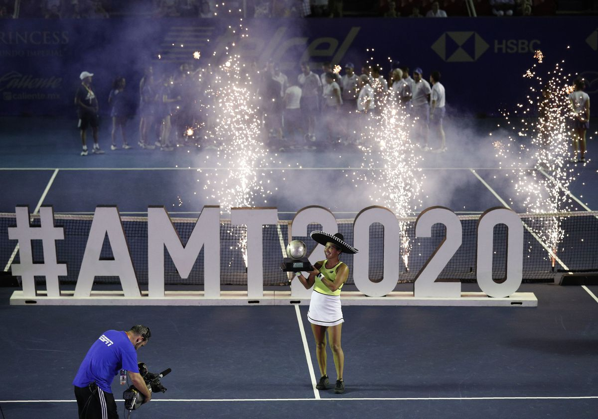 Wearing a sombrero and with fireworks going off behind her, Heather Watson holds up the trophy after winning the women's title at the Mexican Open in Acapulco, Mexico.(AP Photo/Rebecca Blackwell)