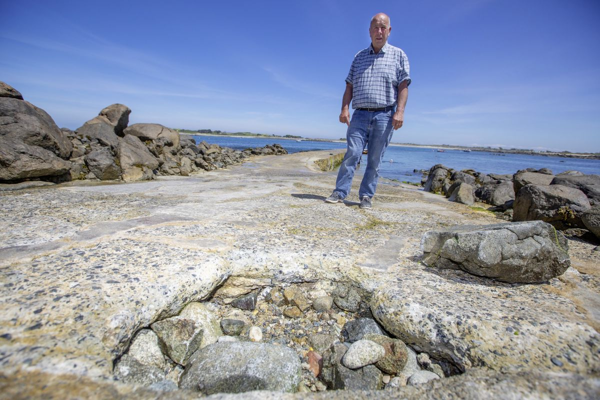 Vale junior constable Bill Cohu at Rousse Pier where a large hole has opened up. Local fishermen have filled the hole with rocks as a temporary fix. (Picture by Peter Frankland, 29659931)