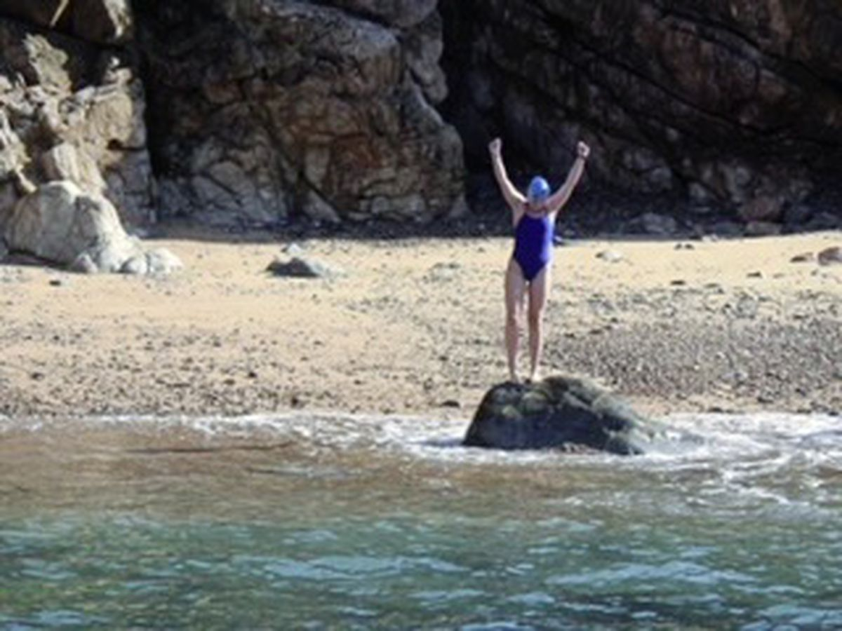 A triumphant Delphine Riley after picking up a pebble on Alderney's Trois Vaux Bay to complete her swim.