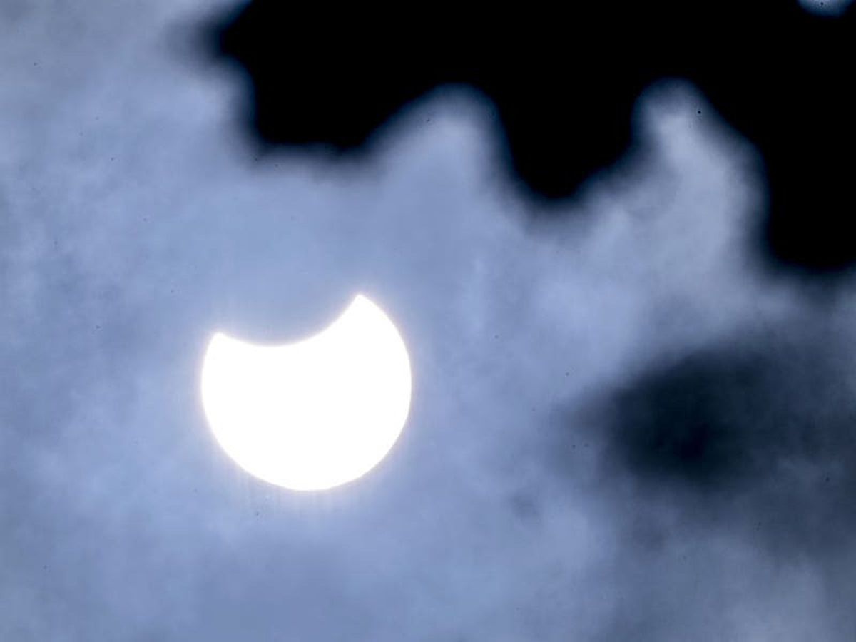 Partial solar eclipse delights UK skygazers as observers see crescent sun