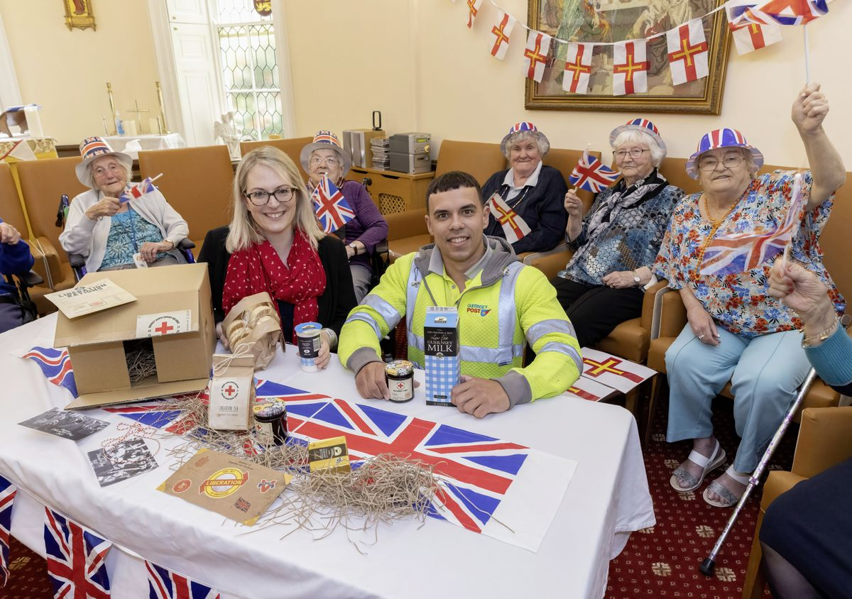 St John's Residential Home residents were given a sneak preview of the Red Cross-style hampers. There will be 50 of them delivered specially today by Guernsey Post. Pictured with the residents are Dawn Gallienne, head of corporate engagement at Guernsey Post, and postie Stefan Bourgaize.