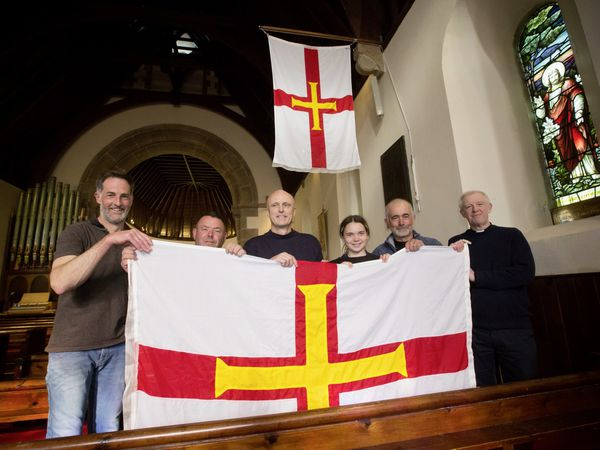 Castel rector the Rev. Scott Lamb, right, with the flag which will hang in St Matthew's Church before being taken out to Grosse Rocque. Left to right, Matt Dorey of Fusion Engineering, who made and fitted the flagpoles in the church, boatman Matt Le Page, who will be taking the flag out to Grosse Rocque, Richard Pearson, whose idea it was to put up a flag in the church, Neve Benstead, 15, and her father Paul, also a boatman, who will be helping take the flag out. The flags have been provided by Roy Bisson. (Pictures by Adrian Miller, 29500083)
